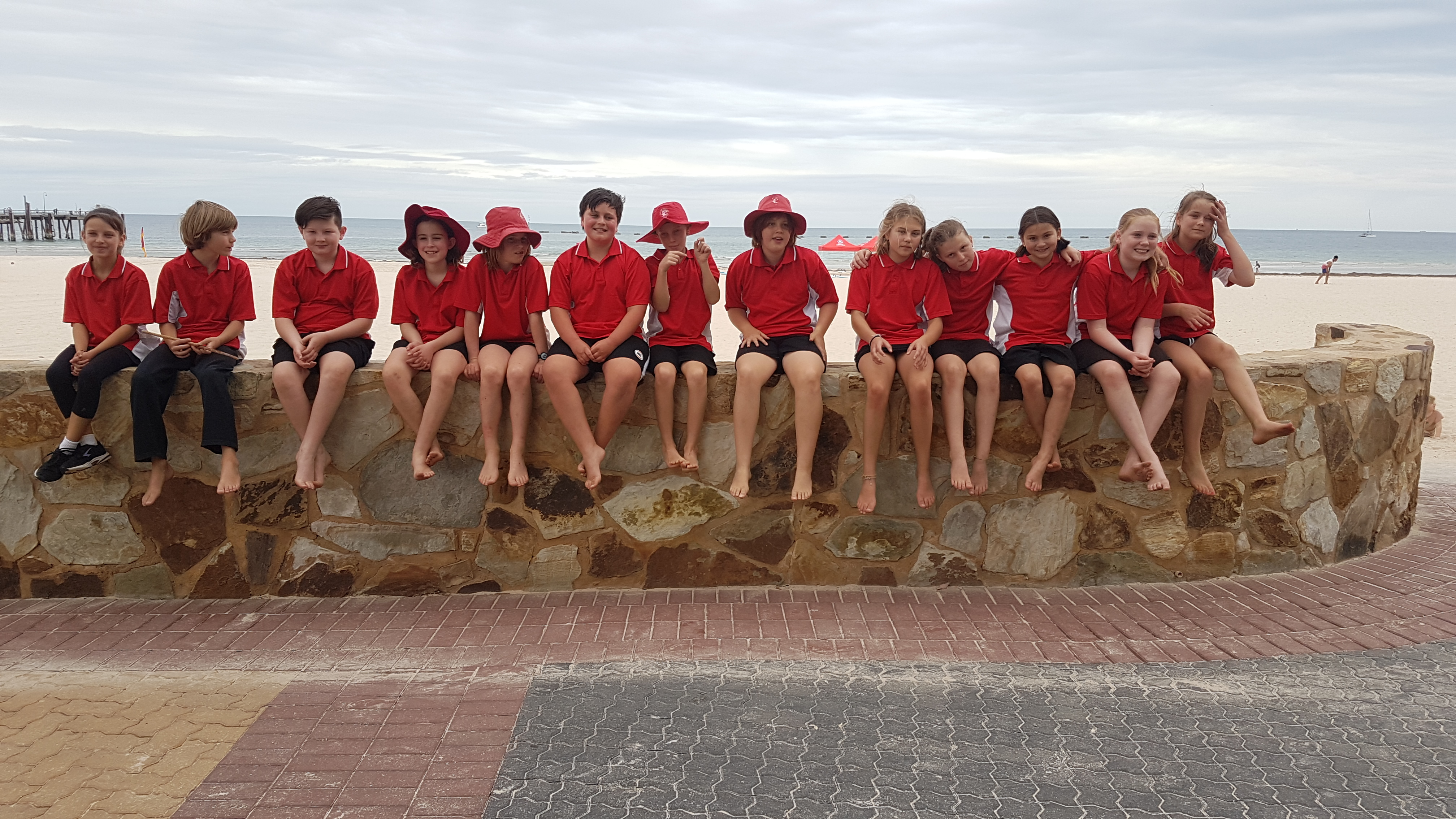 Group of children in red shirts and hats from Scott Creek Primary School sit on wall at the beach foreshore.
